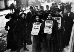 A group of men and women marching with strike ...