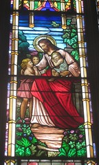 A stain glass rendition of Jesus blessing the children