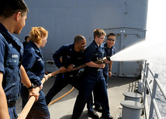 Sailors practice handling a charged fire hose ...