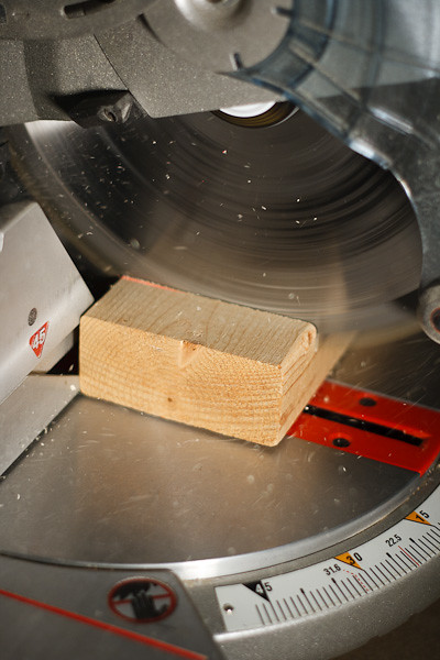 A circular saw mid-cut, sawdust flying.