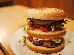 Picture of a rather tall beanburger, stuffed with toppings.
