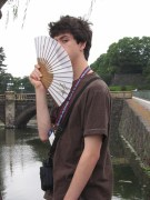 A portrait of me holding a folding fan to my face