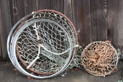 Hoops, Large and Small: Netted hoops for fishing leaning against a weathered wooden wall