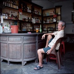traditional chinese liquor shop (lcy) Tags: 6x6 tlr mediumformat candid ishootfilm unesco worldheritagesite squareformat nostalgic oldpeople kodakportra160vc melaka malacca 120mm oldshop c41  vanishingtrade epsonv700 dyingtrade mamiyac330f sekor65mmf35 traditionaltrade malaysia2010
