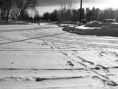 Tracks and footprints in the snow in the parking lot outside the Science Building at UMM