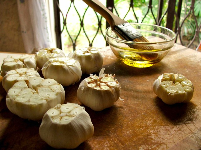 basting garlic flowers with olive oil
