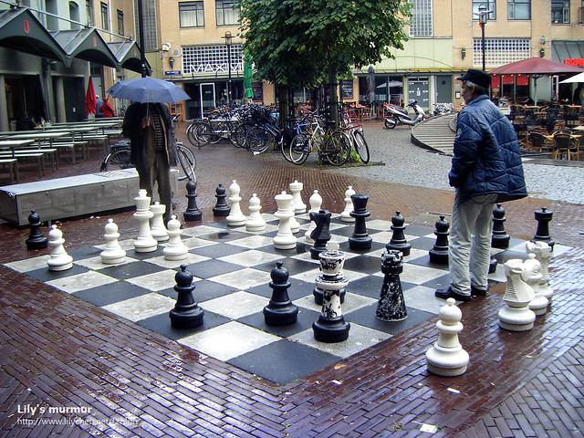 在阿姆斯特丹大街上下棋的兩位老先生,他們很認真,旁邊也有不少人在觀戰。
