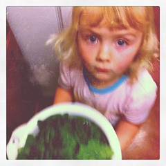 Blurry kid with blurry spinach from the garden.