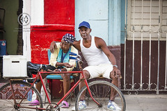 A mother and adult son sit on the street.