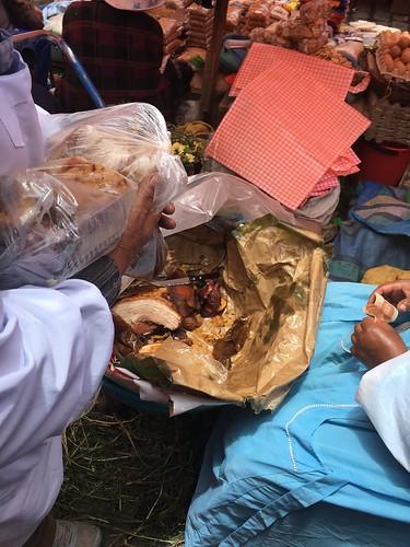 Au milieu de la rue, dans une brouette, une dame distribue de la viande de porc toute chaude !