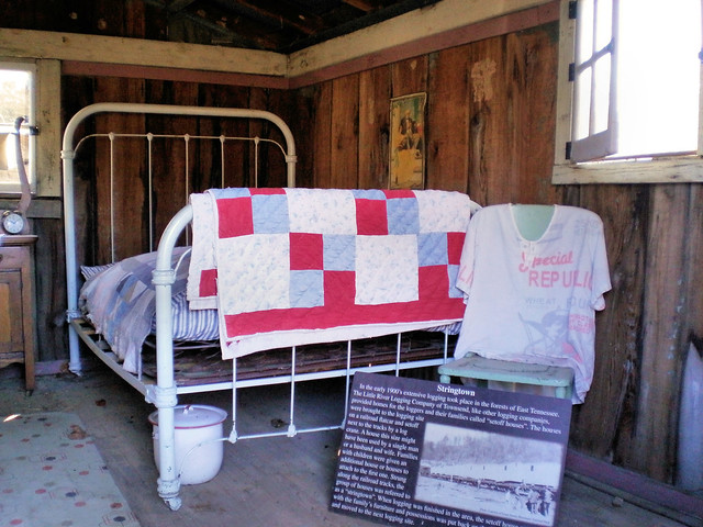 White painted iron bed with homemade quilts and shirt made from flour sacks