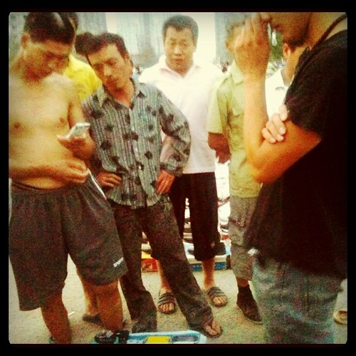 fieldwork: migrant construction workers looking at 2nd hand feature & smartphones, China