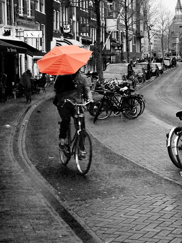 Cyclist cycling through rain with orange umbrella in Amsterdam - Amsterdam Cycle Chic