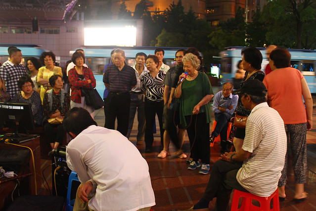 Elderly people gather for a karaoke session on the street at night