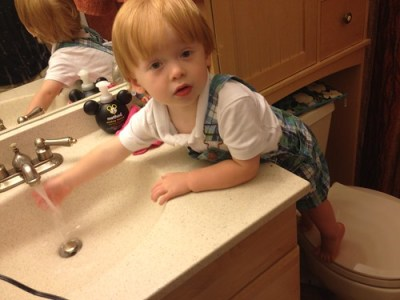 Riley playing with the sink in the bathroom