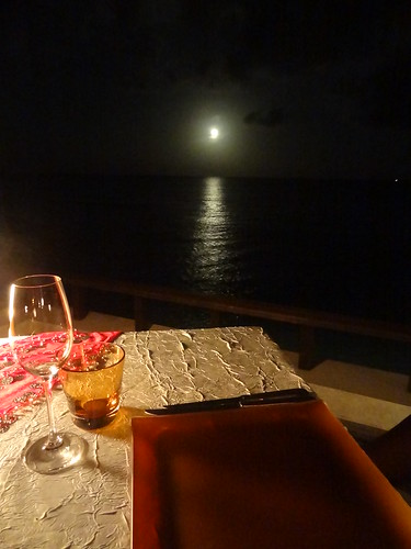 Dinner table on the deck by the water under a full moon.