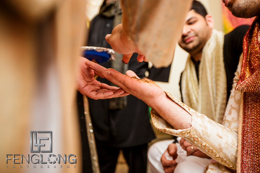 Giving groom henna during Mehndi night at Ismaili wedding