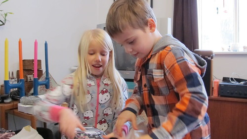 Karítas and Adrían assist with the gift opening