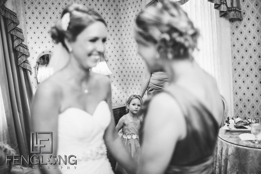 Flower girl looks on as bride puts on her wedding dress