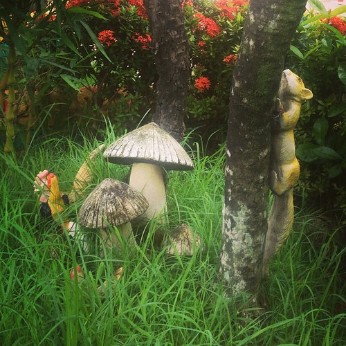 Thai temple kitsch. Chickens, mushrooms and a squirrel tied to a tree.