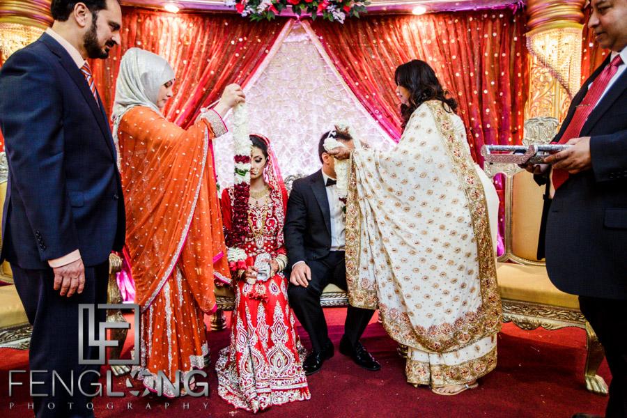 Bride and groom receive wedding garlands from parents