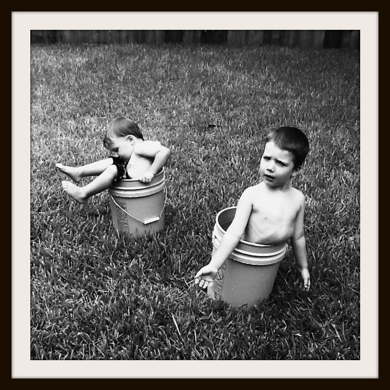 Young boys cooling off in the back yard by getting into 5 gallon buckets full of water.