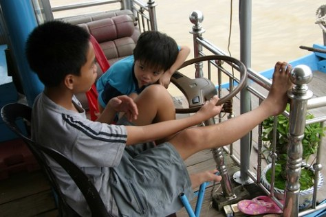 Boys navigate down the Perfumed River, Hué, Vietnam