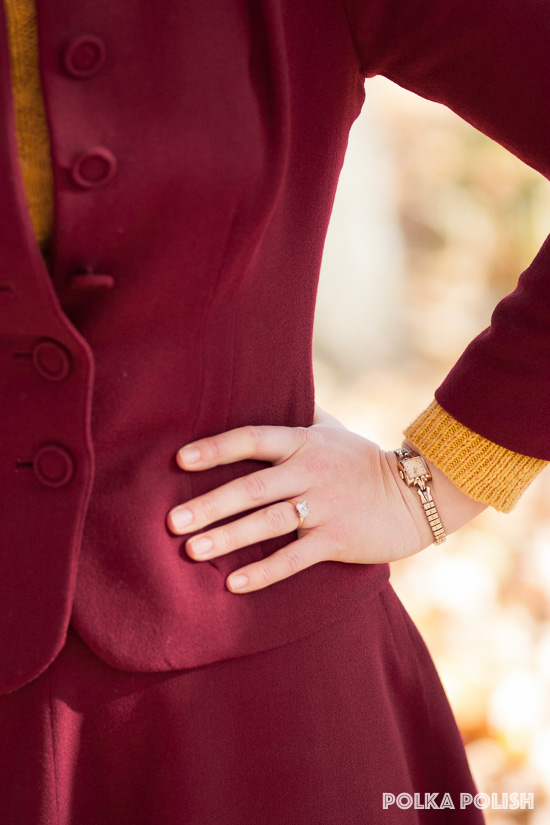 A dainty 1940s vintage wristwatch is paired with a red suit and yellow sweater