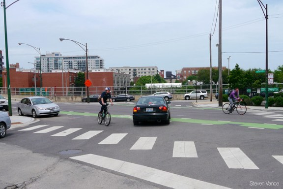 Two bicyclists take different routes around this driver blocking the bike lane with their car
