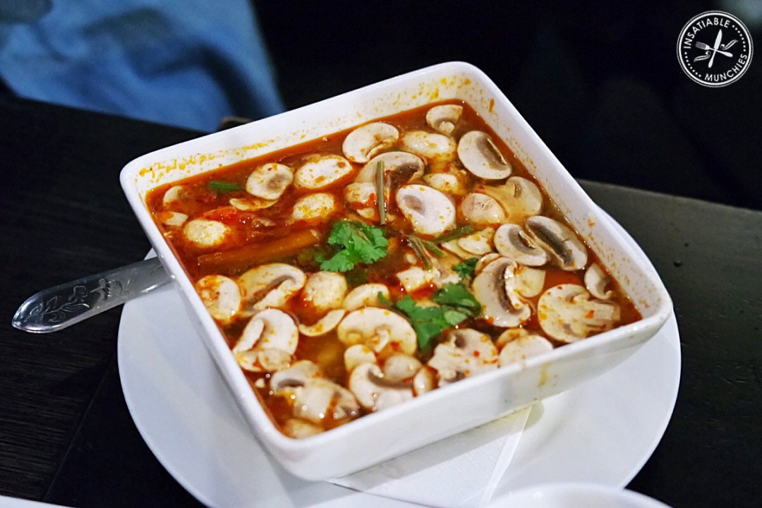 Tom Yum Goong - a hot and sour prawn soup that's flavoured with lime and lemongrass - sits in a large square bowl with button mushrooms and garnished with coriander.