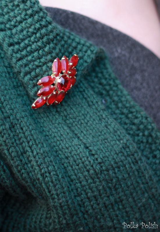 Vintage red glass brooch in an abstract starburst or flower design pinned on a green knitted sweater