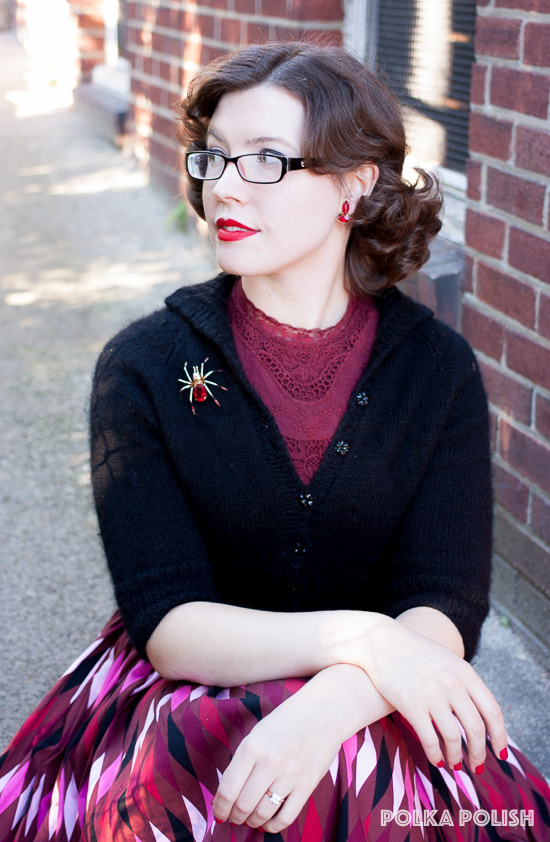 A mostly modern 1950s inspired outfit in red and black, with a harlequin skirt from Pin Up Girl Clothing and handknit black raglan sweater paired with a vintage costume jeweled spider brooch