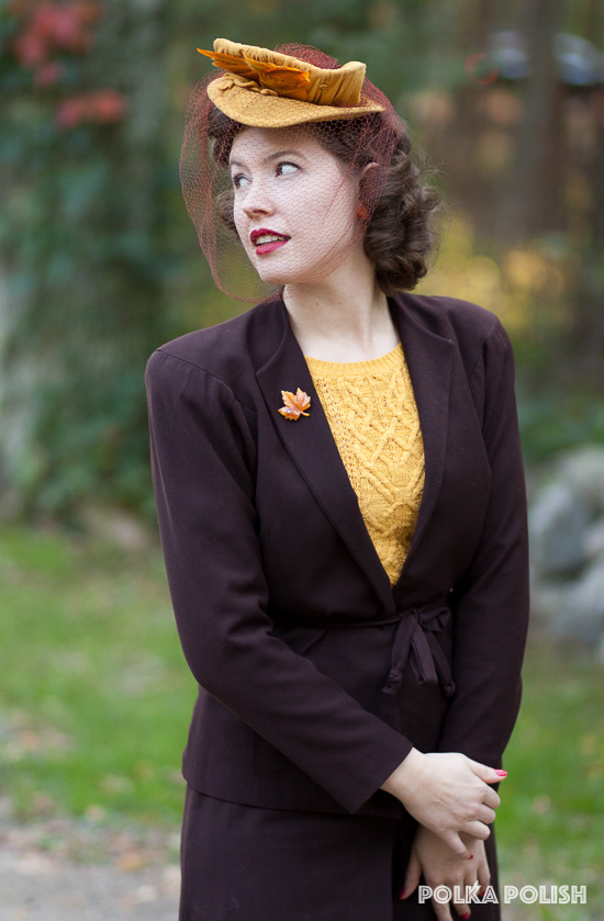 A vintage autumn ensemble featuring a brown 1940s suit with a goldenrod tilt hat and sweater