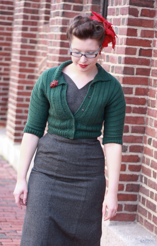 Festive vintage holiday outfit with enormous faux poinsettia, red jewelry, grey dress, and green sweater