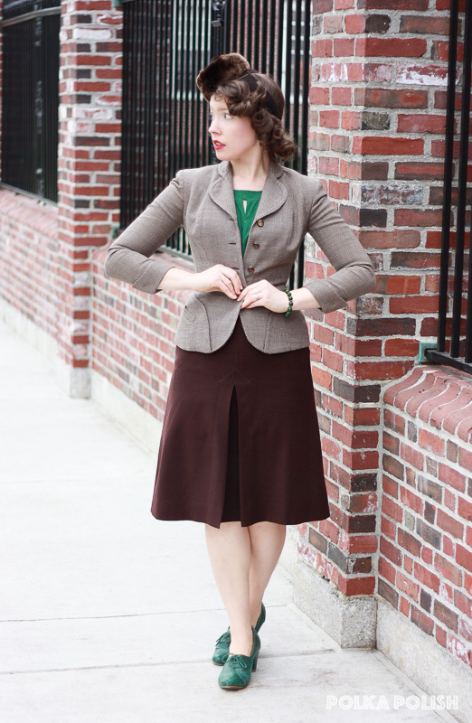 A brown 1940s mismatched suit styled with a fur tilt hat and green accessories