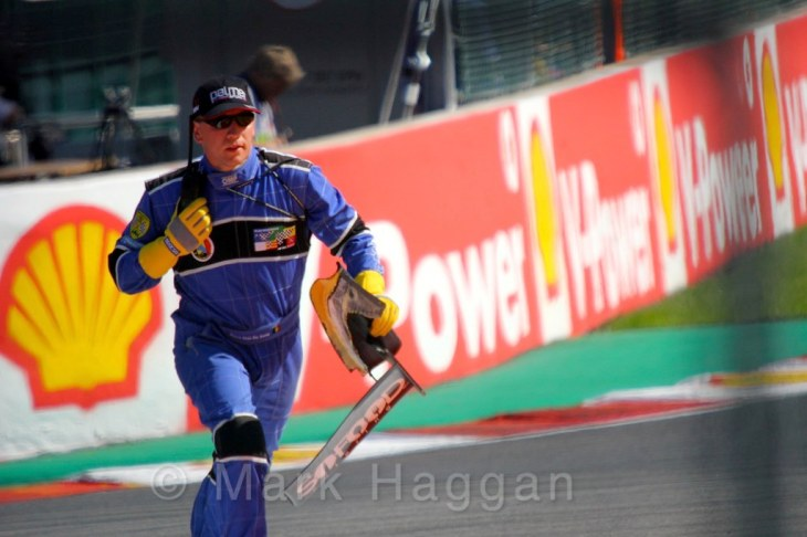 A marshal recovers debris in the GP2 feature race at the 2015 Belgium Grand Prix