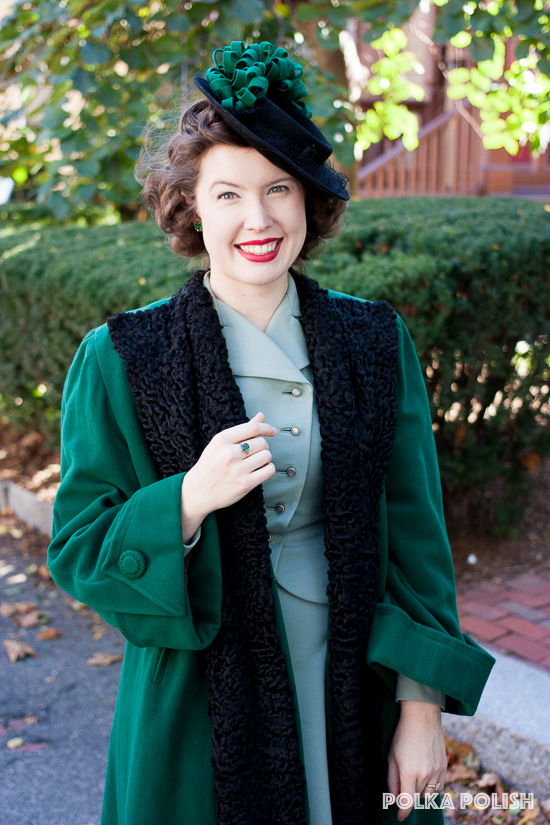 A black tilt hat is topped with rows of green felt curls to match a vintage 1940s green swing coat trimmed with curly lamb
