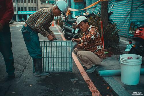 正在將水溝蓋加上網子的工人。