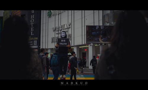 人來人往的西門町,有位戴著V怪客的面具大哥在宣傳素食,背上就印著純素主義,而一旁拿著吃到飽廣告牌的工讀生就來坐在他隔壁,這對比真強烈。
