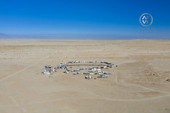 A group of campers line up their motorhomes in a circle in the desert.