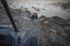 An off road vehicle descends down a hill in the desert.