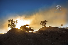 An off road vehicle climbs up a hill in the desert.