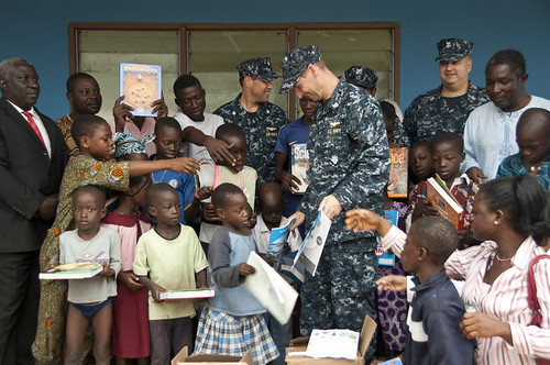 Sailor hands out school books to children in N...