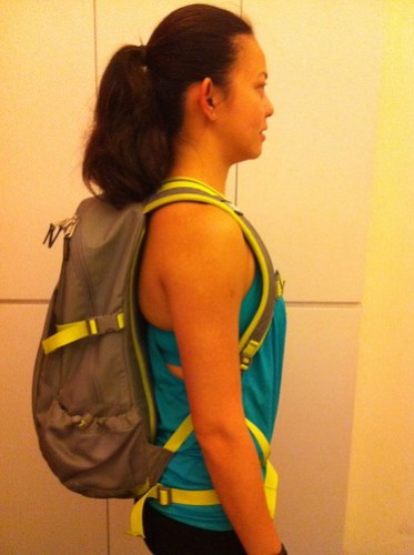 Adeline- side profile of her carrying a backpack correctly using chest belt an waist belt.