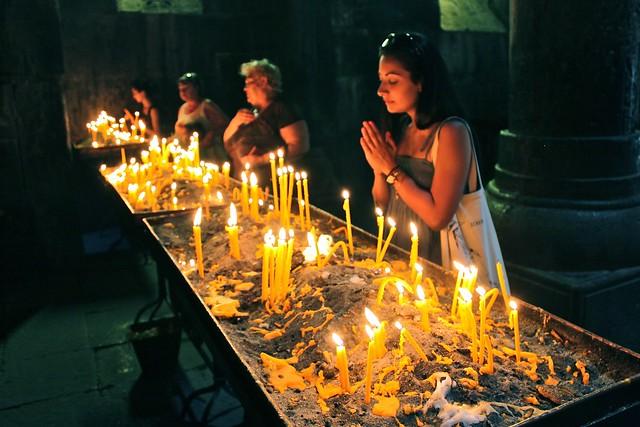 Une fille qui prie, monastère Geghard, Arménie