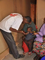 An MSF health worker examines a malnourished child