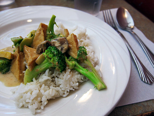 Tofu and broccoli in a peanut sauce sits atop a bed of white rice.
