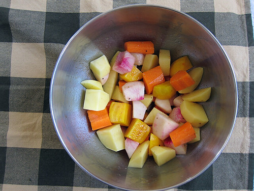 A metal bowl half-filled with chunks of colorful, cubed vegetables.