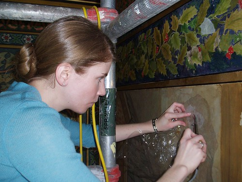 Stephanie setting down flaking paint with a tacking iron