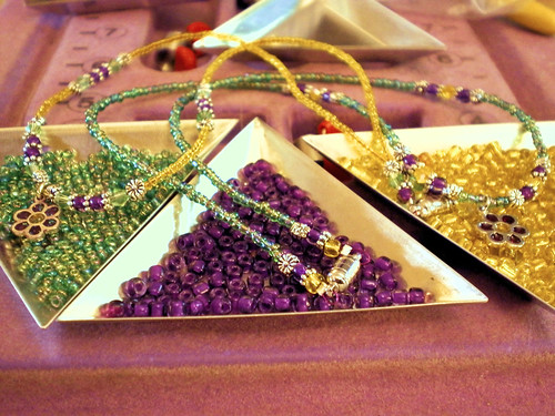 Green, purple, and yellow beads in triangle dishes with necklaces of those colors draped over them holding flower charms.
